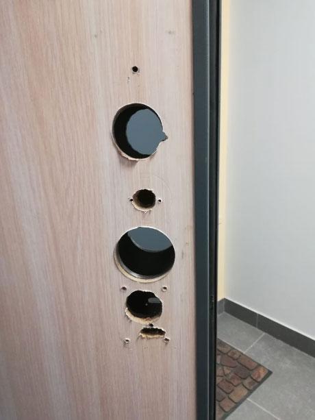 Металлическая дверь с отверстиями от двухсистемного механического замка